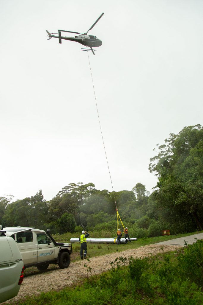 workers preparing power-line pole for helicopter craning