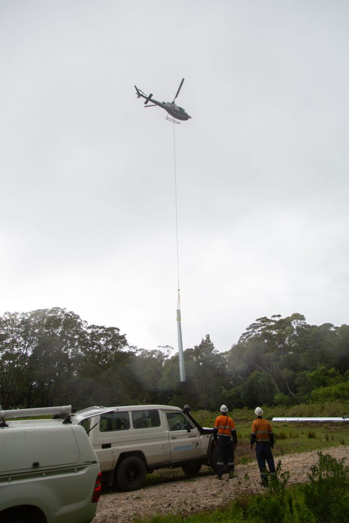 a helicopter craning powerline poles across landscape
