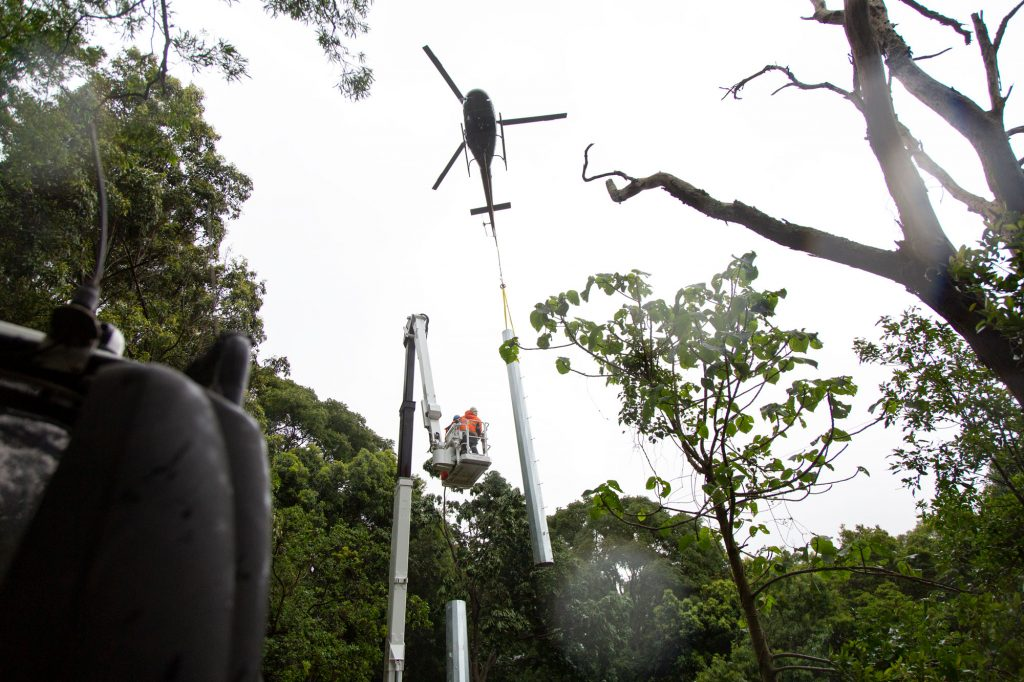 a helicopter craning powerline poles