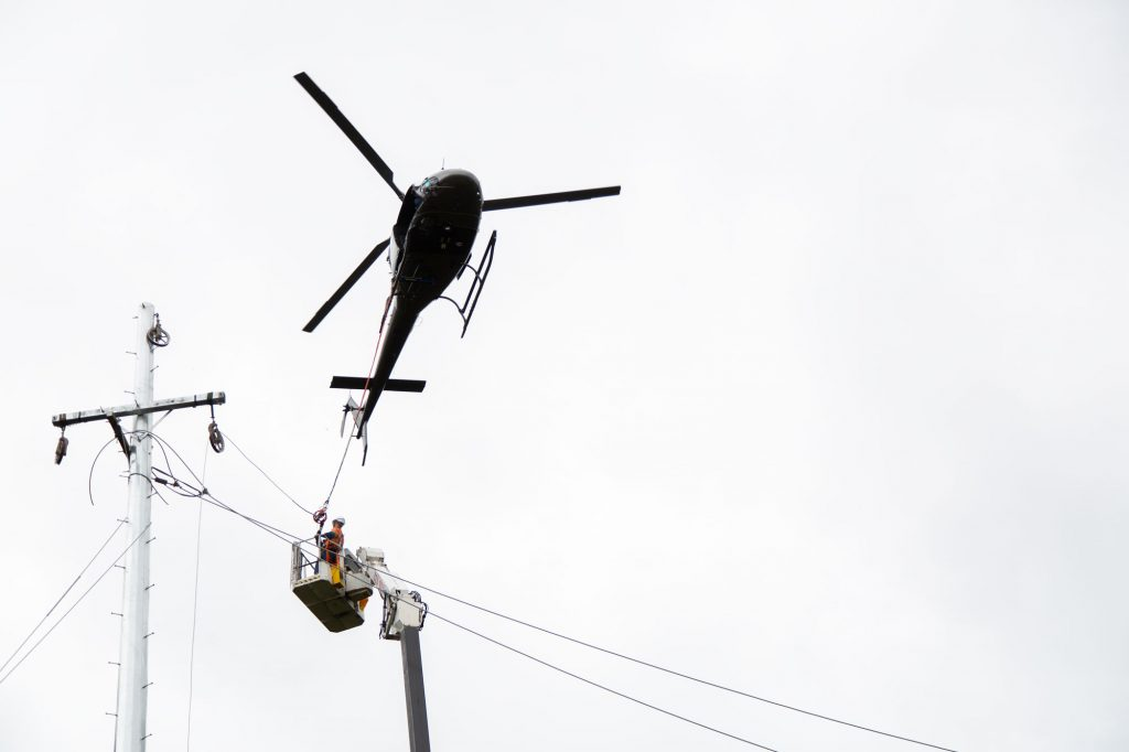 a helicopter assisting cherrypicker installing high voltage overhead powerlines